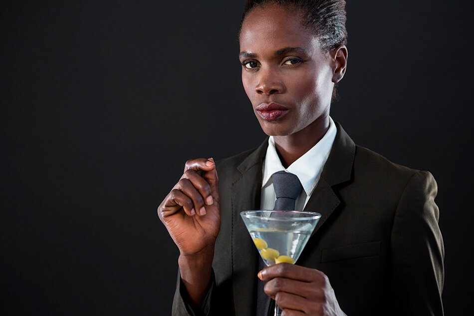 black androgynous person in suit drinking a martini