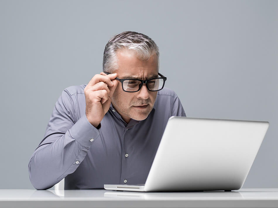 businessman looking at computer wearing glasses