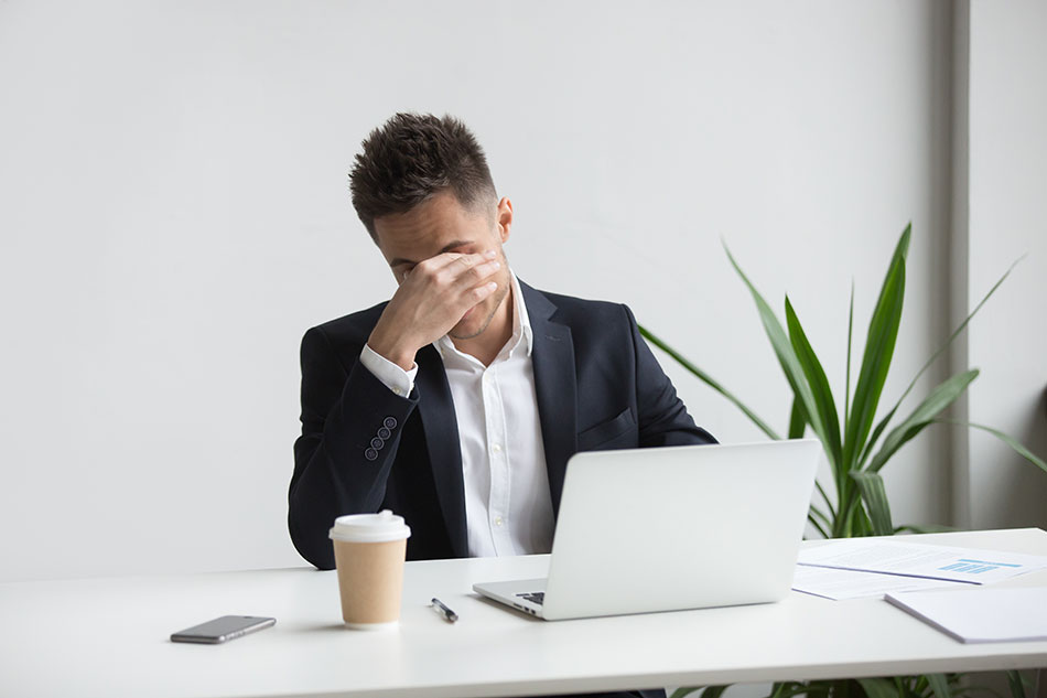businessman rubbing eyes in front of laptop