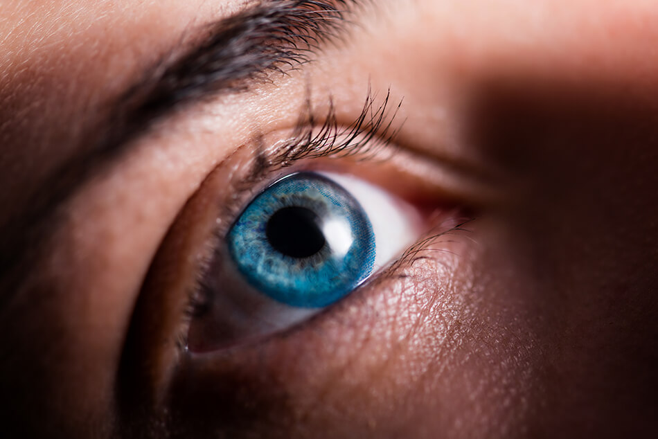 Close-up of woman's eye with a blue contact lens