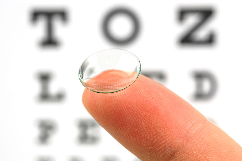 contact lens on finger and eye test chart