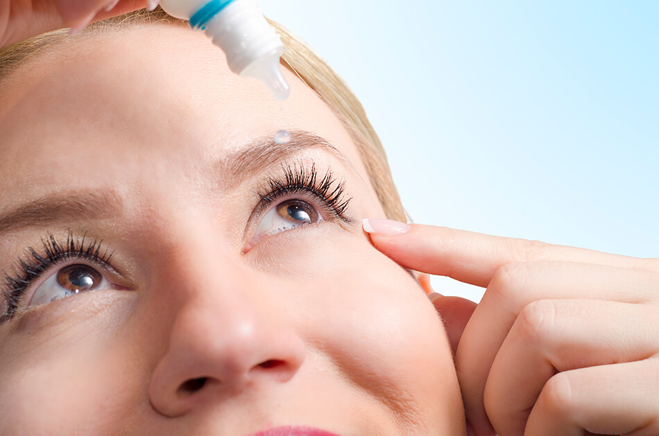 closeup of young woman applying eye drops