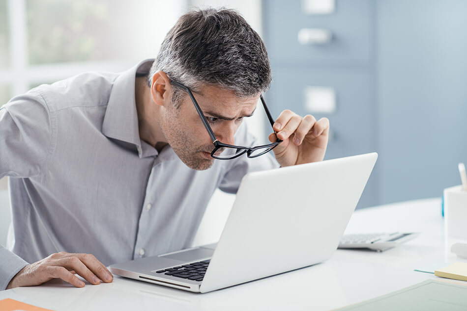 man squinting to see computer screen