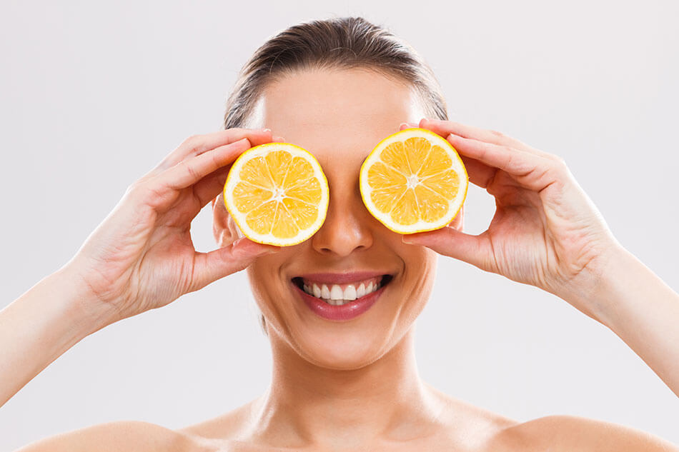 Woman holding lemon slices up to her eyes
