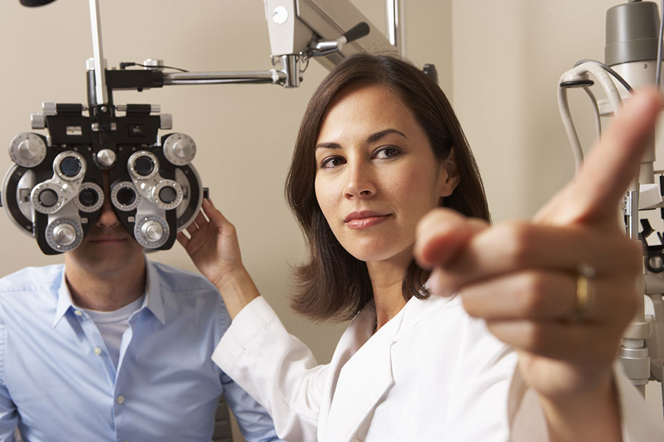 female eye doctor giving man an eye test