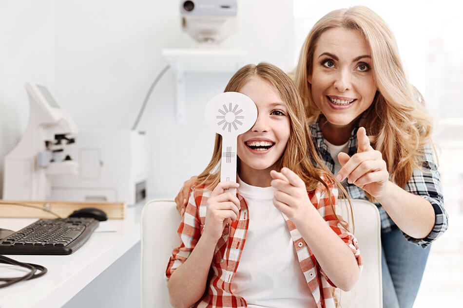 girl smiling with eye paddle along with her mother during eye exam