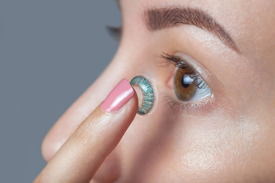 girl inserting coloured contacts
