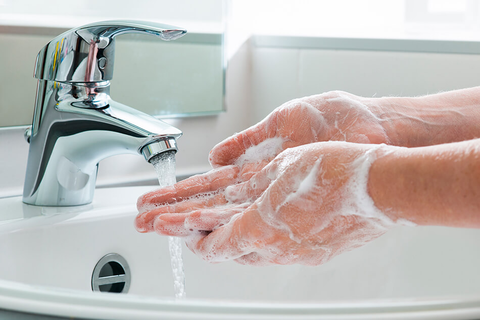 soapy hands under running tap