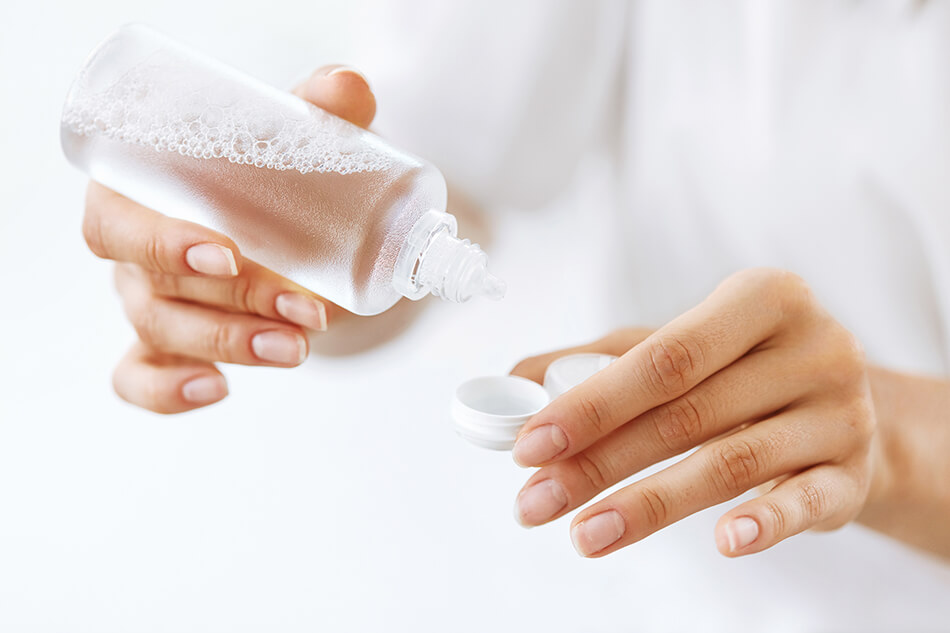 hands pouring contact lens solution in contact lens case