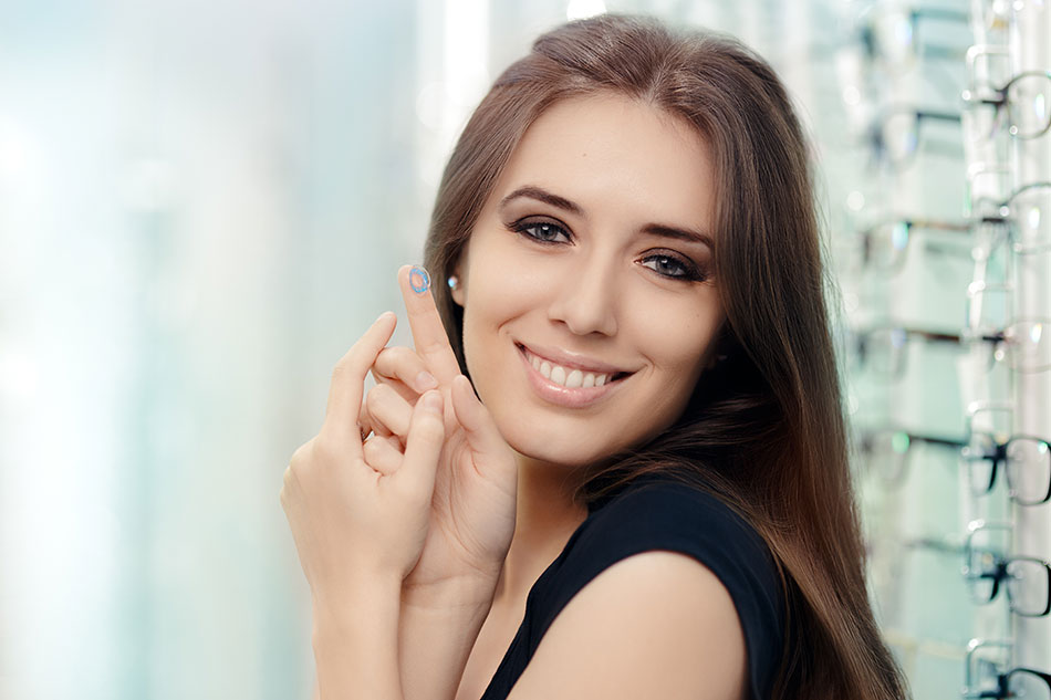 Woman happy to keep her contact lenses breathing, holding one on her finger