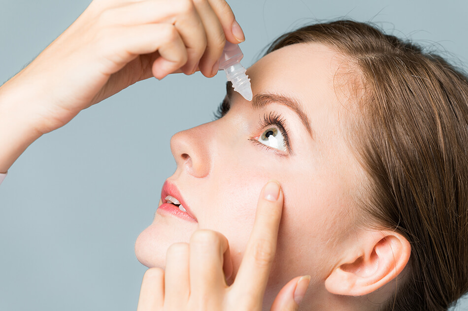 woman wearing contact lenses and using eye drops