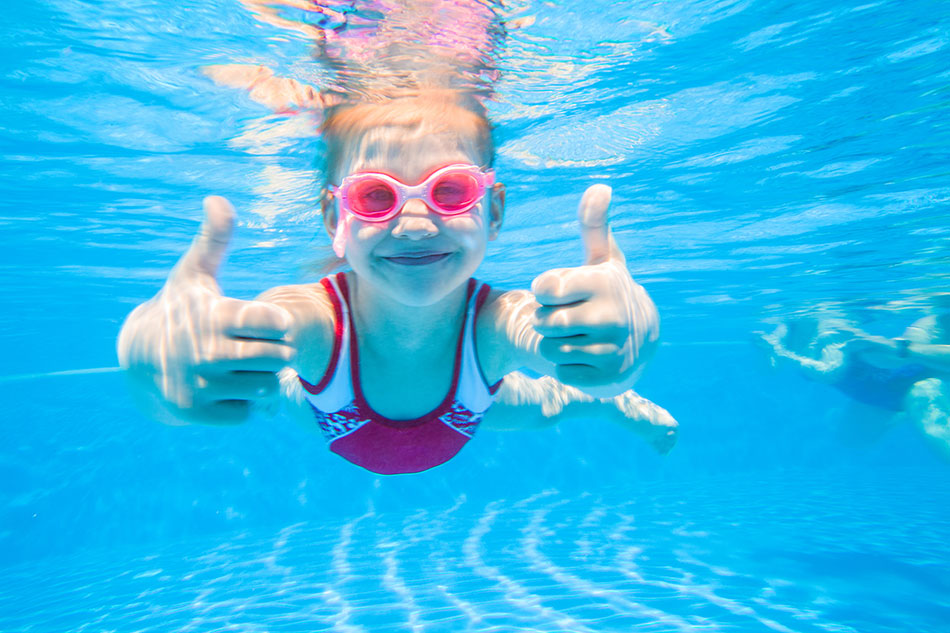 Little girl wearing goggles underwater giving thumbs up