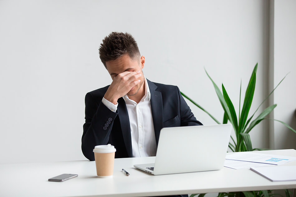 man at computer resting his eyes while getting used to contacts