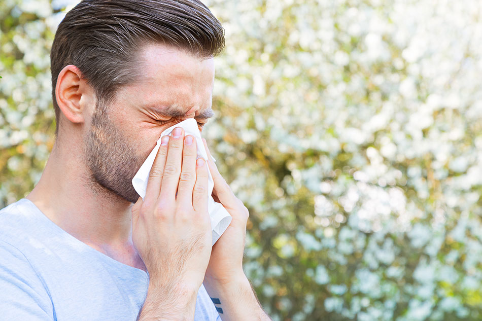 Man with contact lens allergy sneezing into napkin