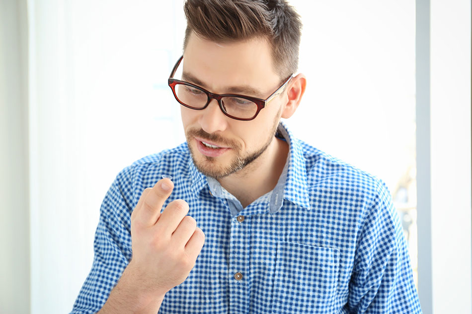 man wearing glasses with a contact lens on his finger