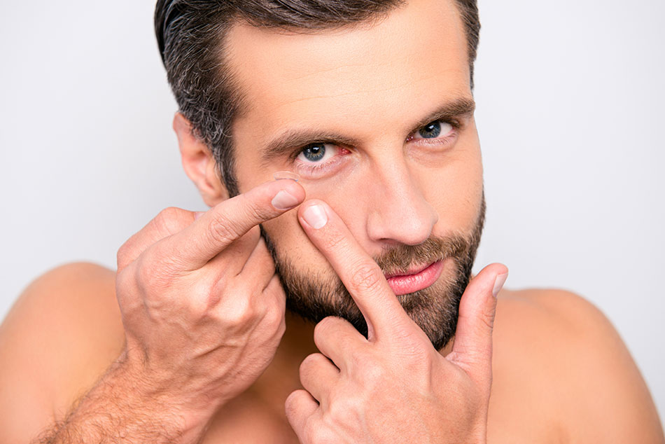 Man putting on contact lens