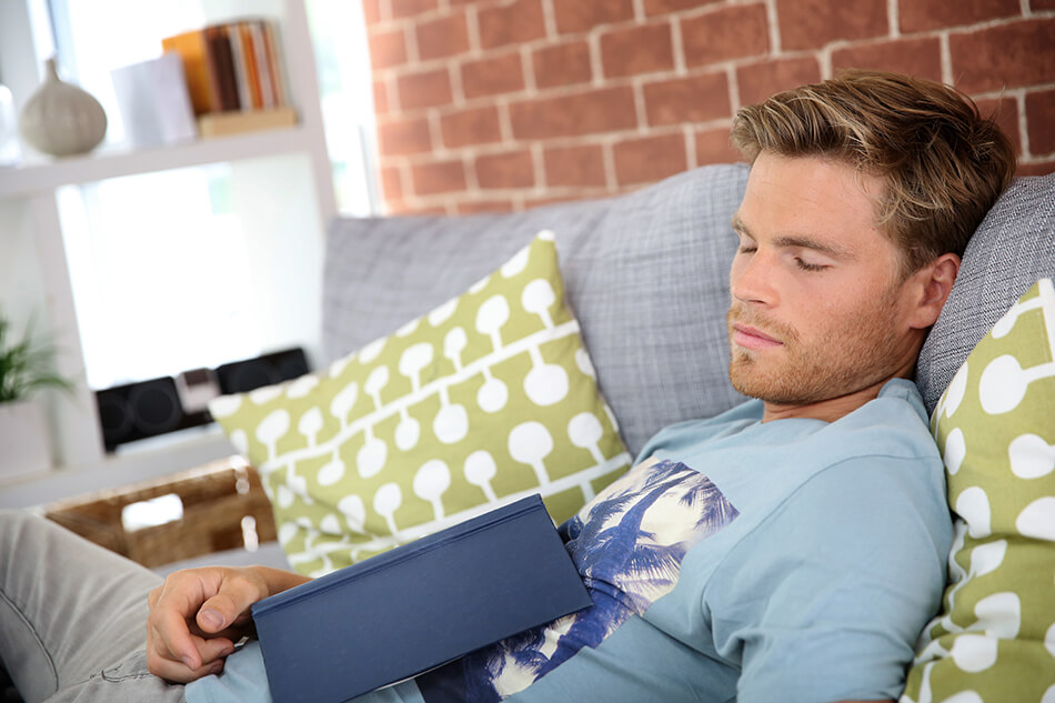 Man napping on couch with a book