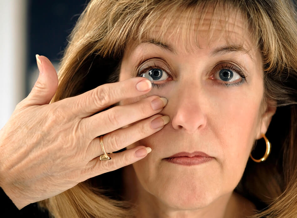 older woman with glaucoma putting in contact lenses