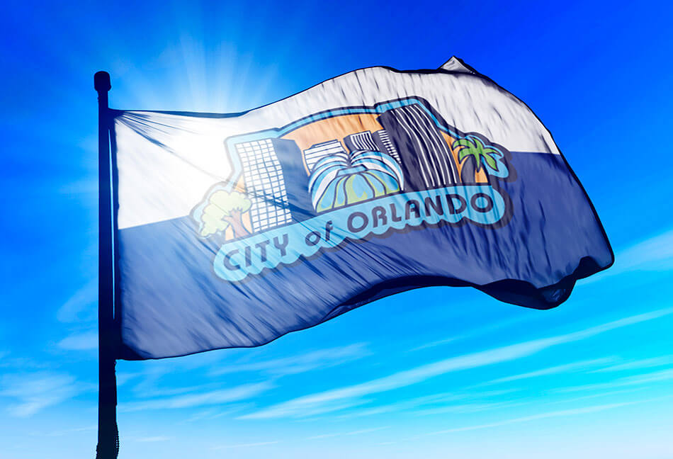 Orlando Flag with blue skies swaying in wind