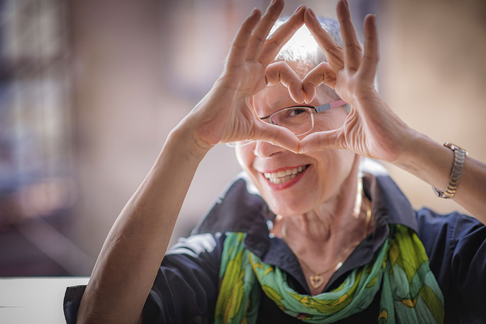 senior woman with glasses making heart shape in front of face