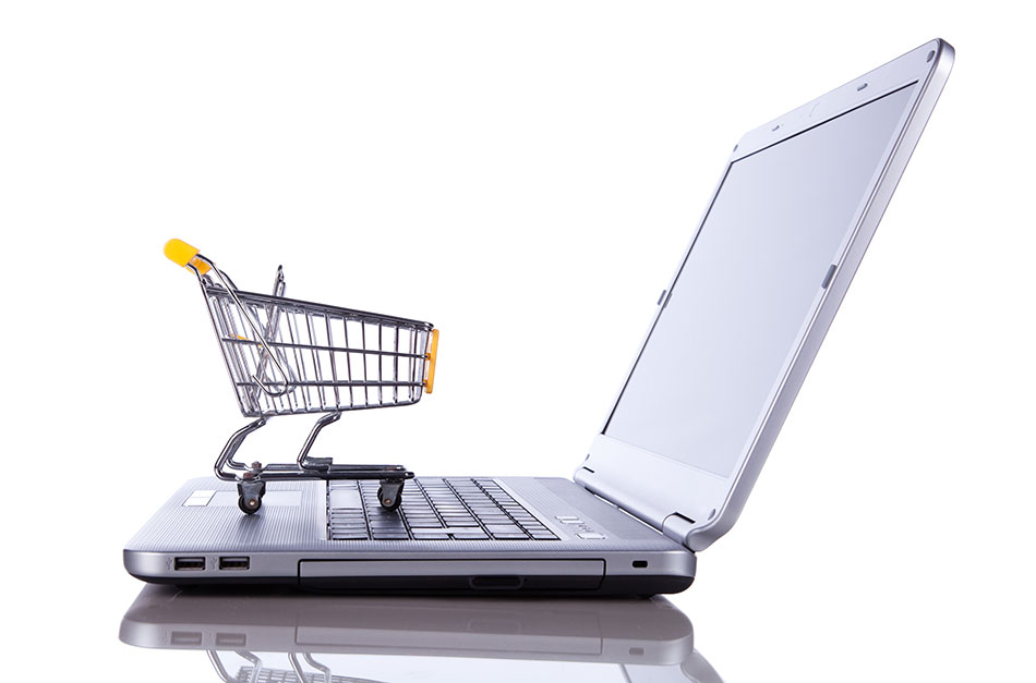 Small shopping cart on keyboard of laptop computer