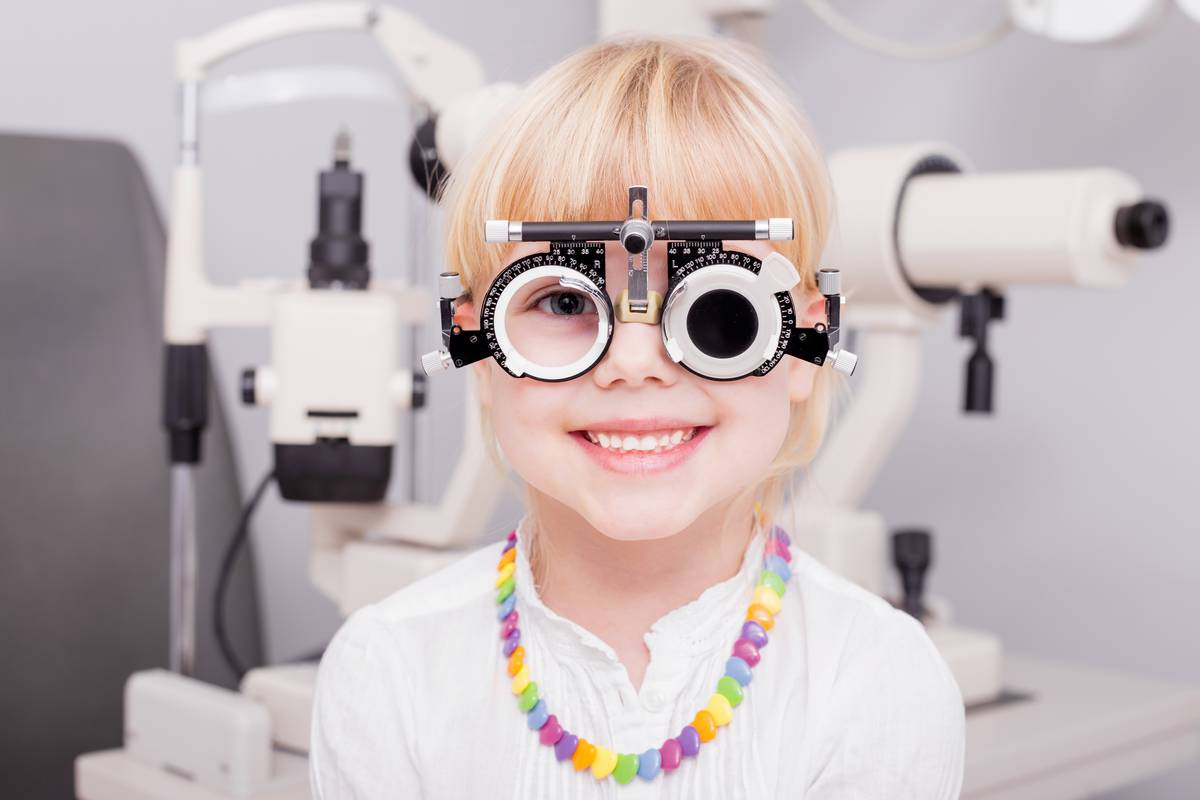 Small smiling child having eye exam