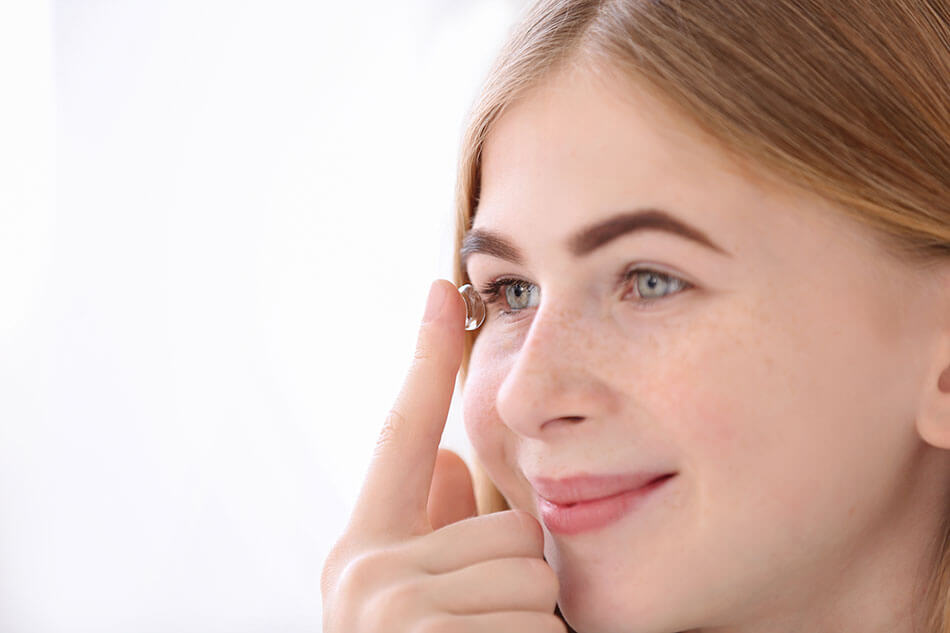 Smiling teen girl putting contact lens in her eye