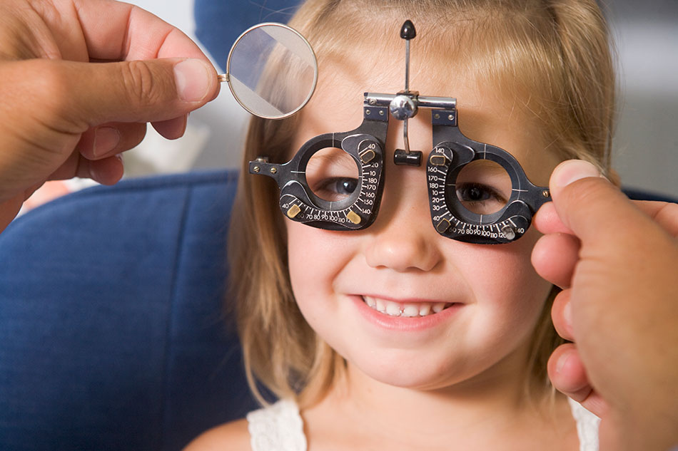 Smiling young girl being examined by optometrist