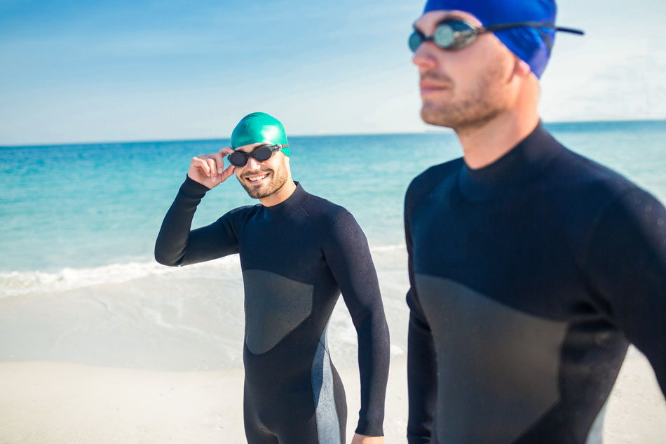 Two men wearing swimming goggles at the beach