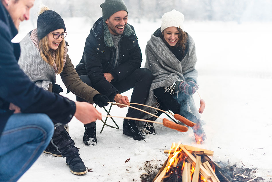 people roasting hotdogs on a campfire in the snow