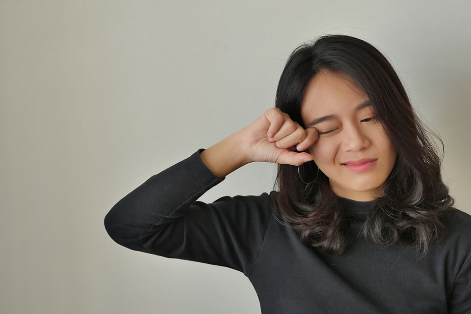 woman in black shirt rubbing her eye