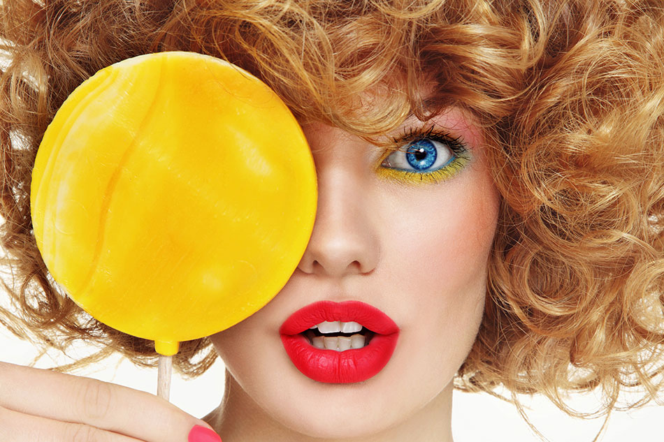 woman with blue contacts and makeup holding lollipop