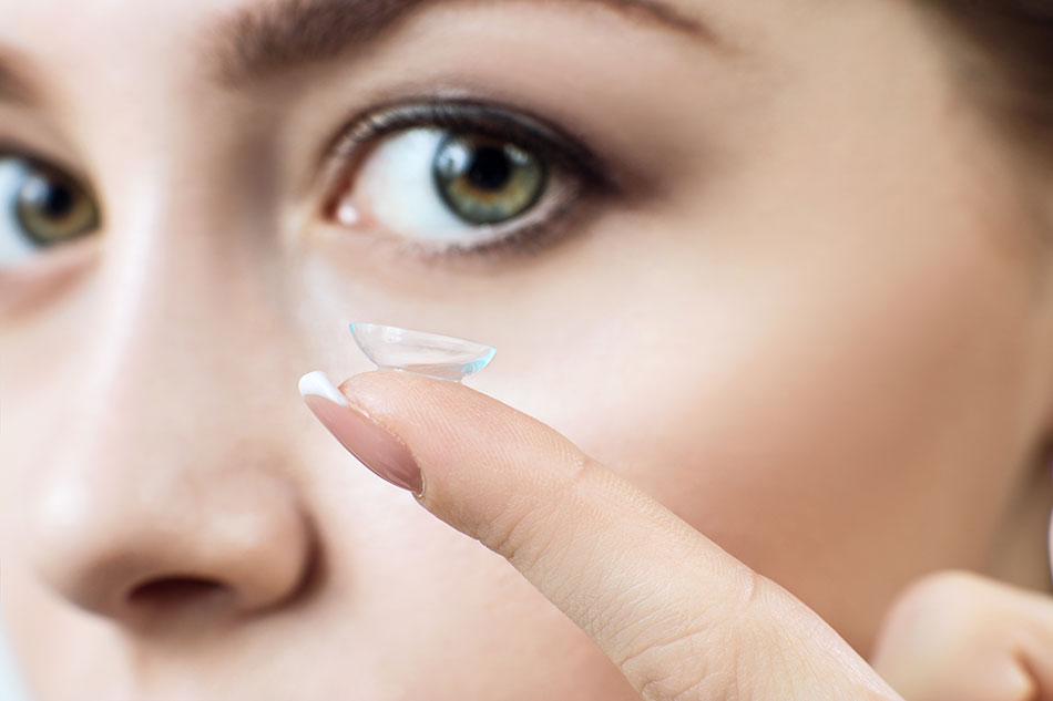woman with contact lens on fingertip