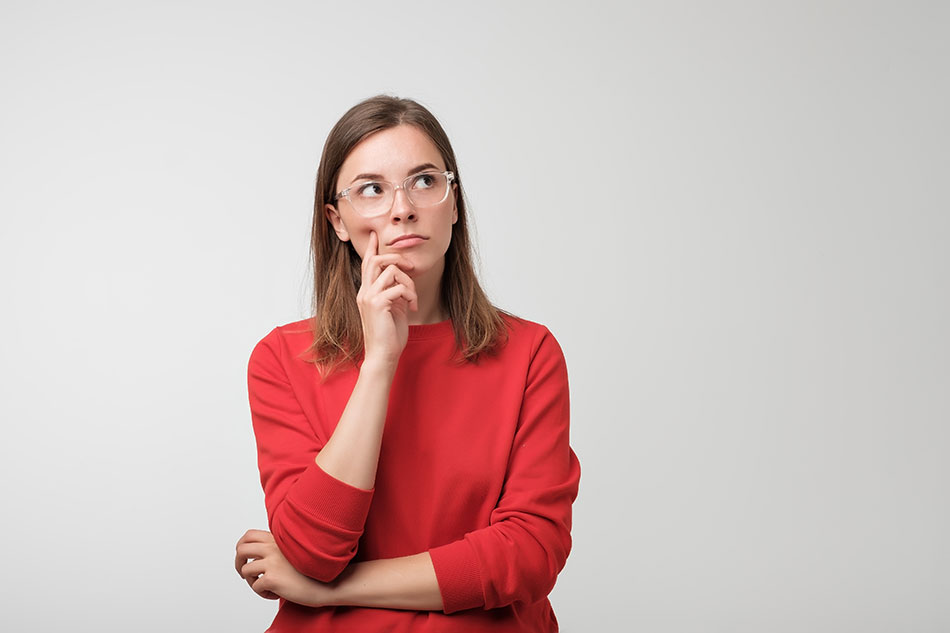 woman wearing glasses thinking about where to get contacts