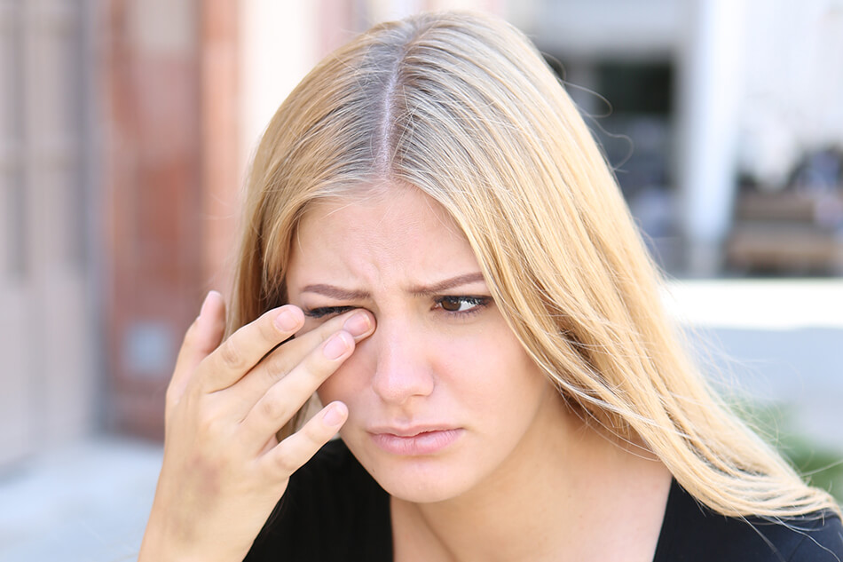 woman with hand to face due to contact lens irritation