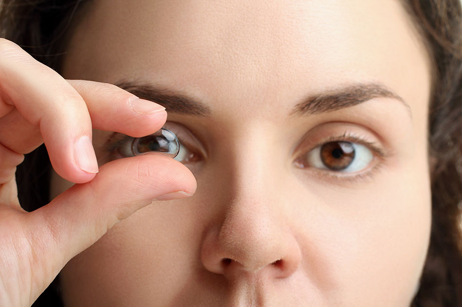 Woman looking through contact lens held up to her eye