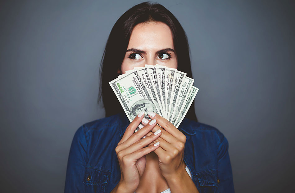 woman holding money in front of face