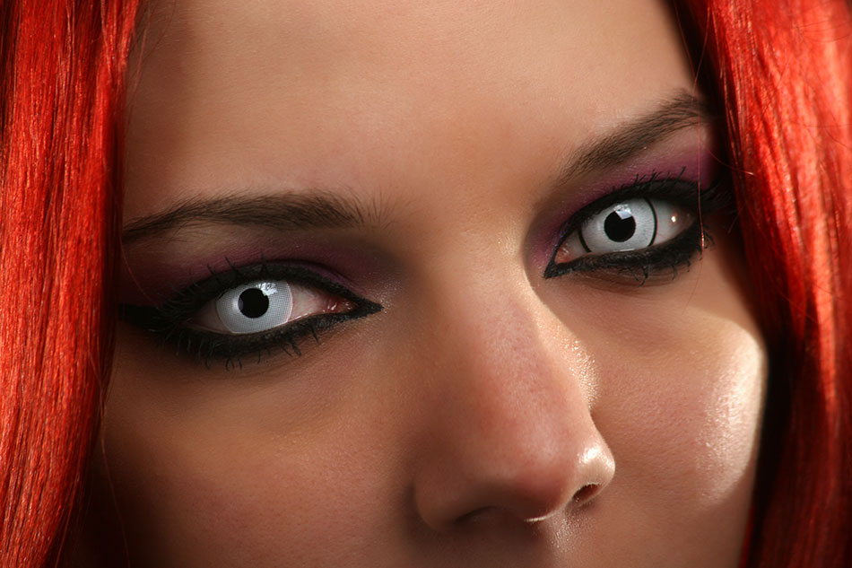 woman with red hair and white contact lenses
