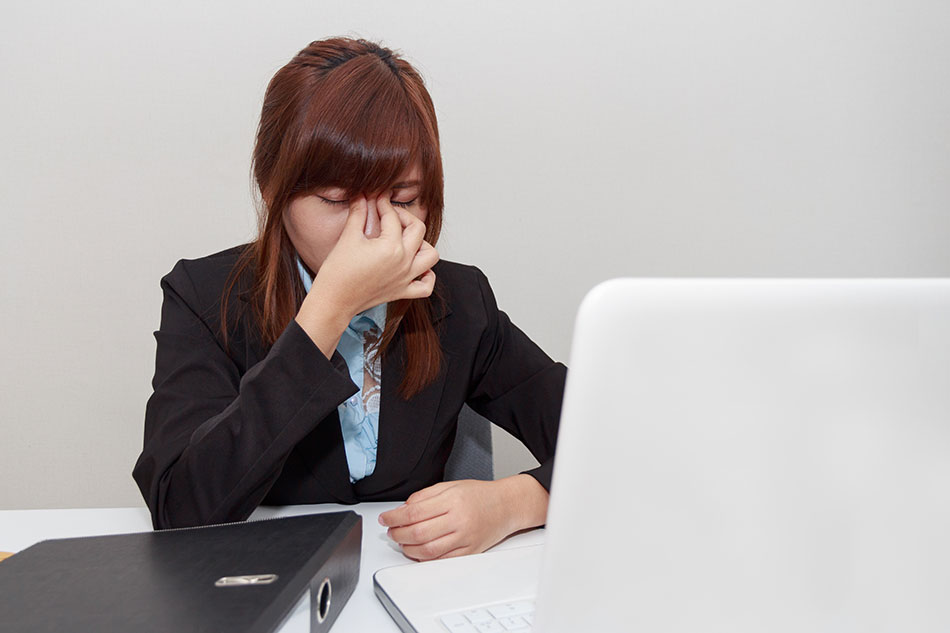 woman at computer rubbing her eyes due to eye strain