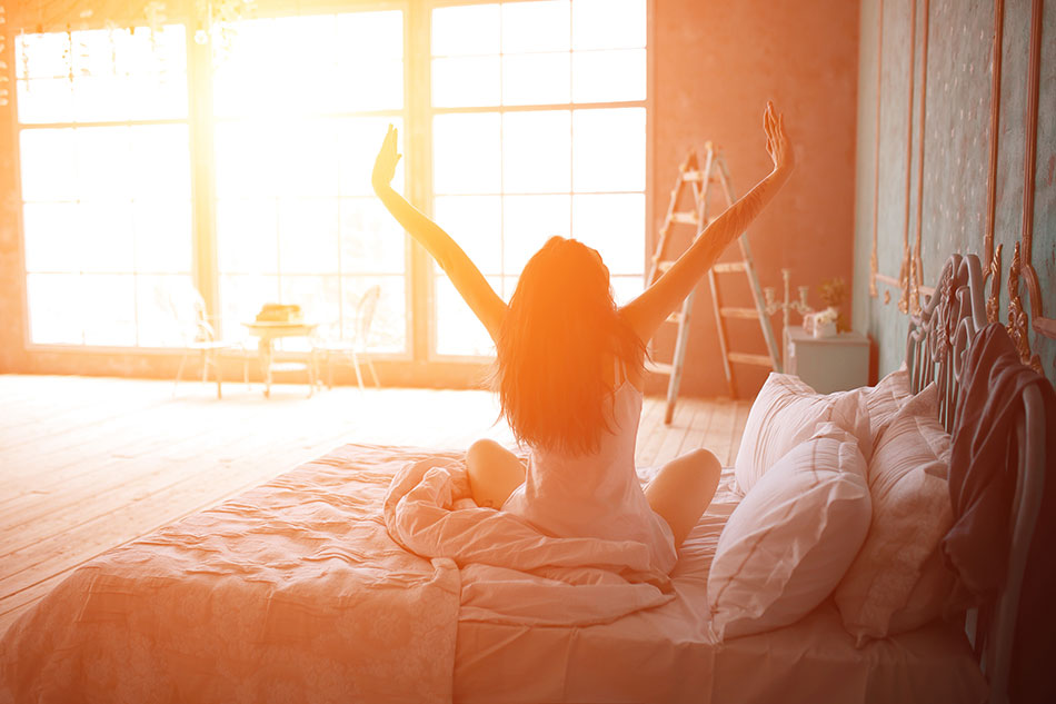 woman stretching on the bed in the morning sun