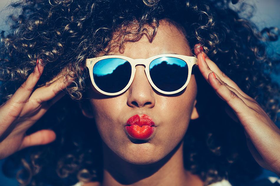 woman with sunglasses blowing kiss