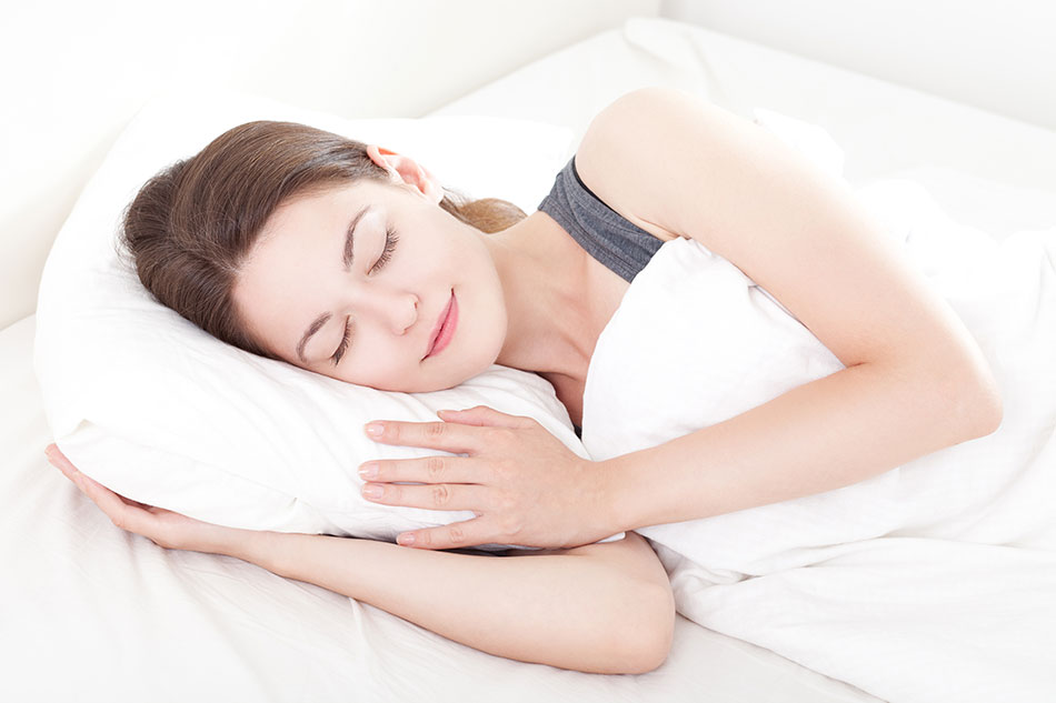 woman in tank top sleeping with hand under pillow