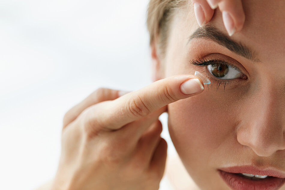woman inserting contact lens into eye