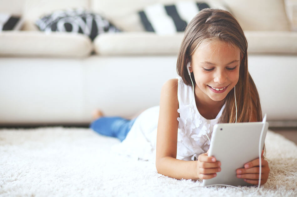 Young girl smiling while on her tablet