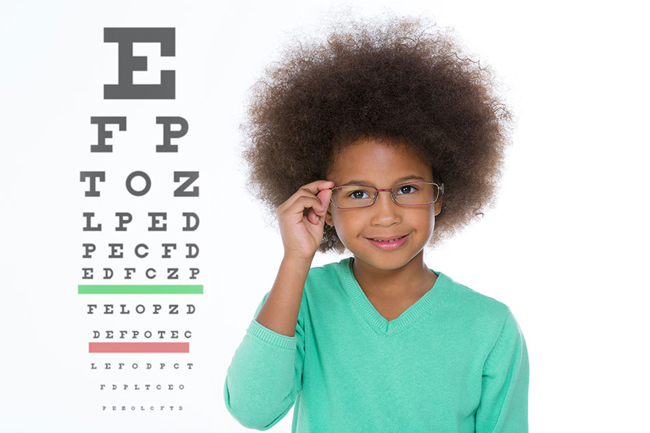 Young girl wearing glasses, eye chart in background