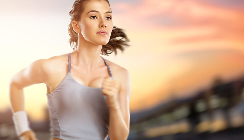 young woman running with colourful sky in background