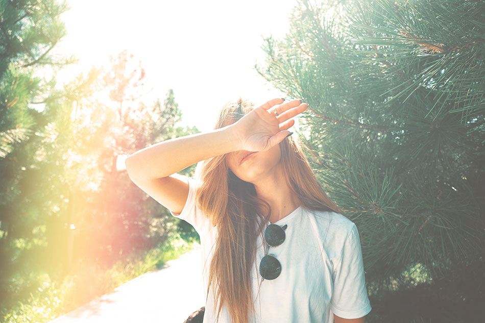 young woman shielding eyes from sunlight